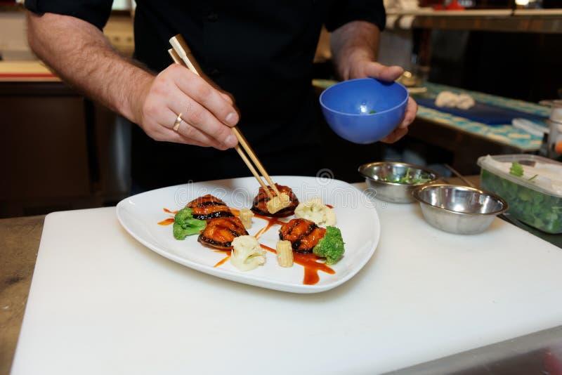 Шеф-повар украшает блюдо с палочками стоковое изображение rf