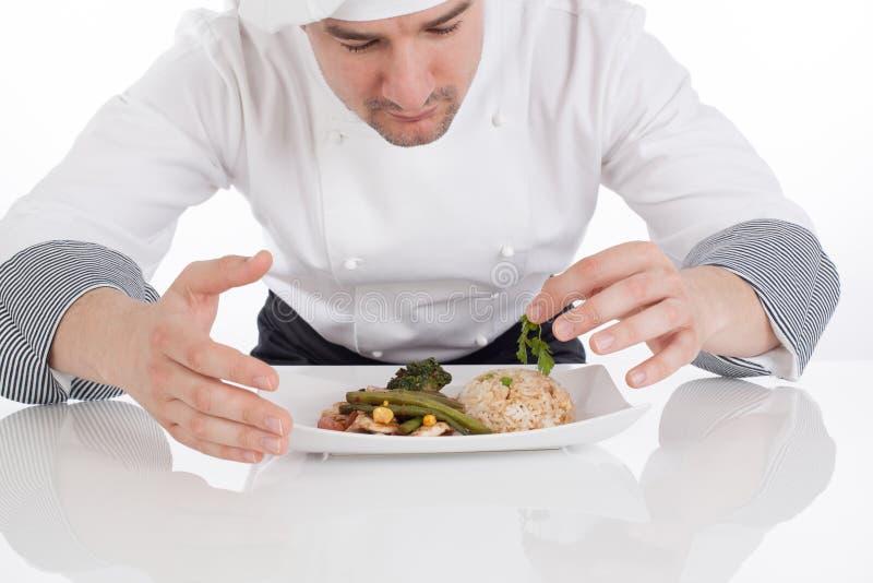 Шеф-повар украшая подготовленную еду на плите стоковое фото rf
