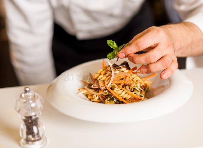 Шеф-повар украшая салат макаронных изделий с травяными листьями стоковые изображения rf