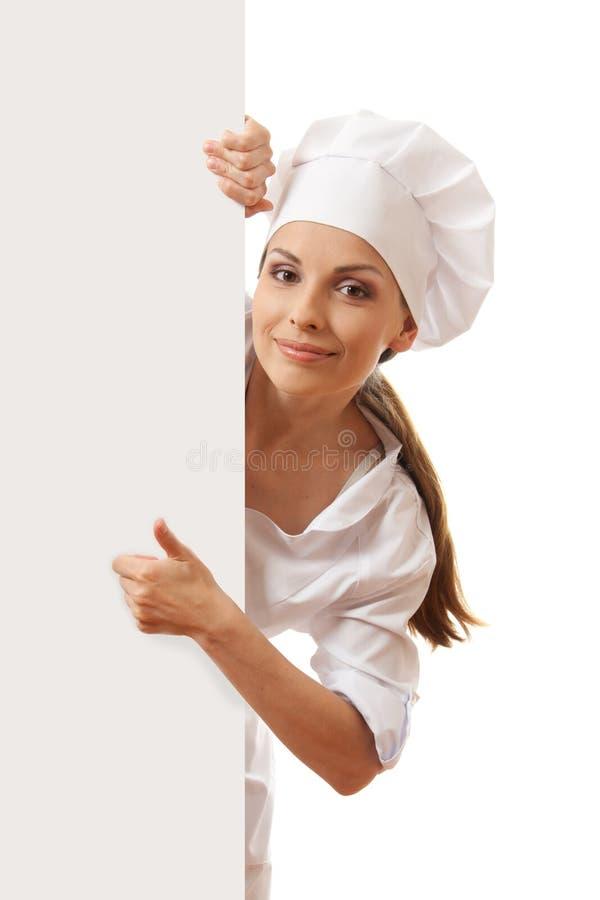 Шеф-повар, хлебопек или кашевар женщины держа знак белой бумаги стоковые изображения
