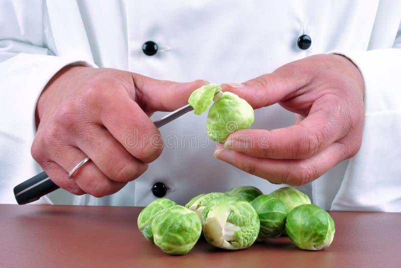 шеф-повар brussels очищает женские ростки стоковое фото