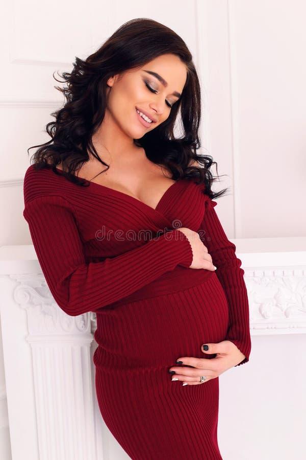 Шикарная беременная женщина при длинные темные волосы представляя на спальне стоковые изображения rf