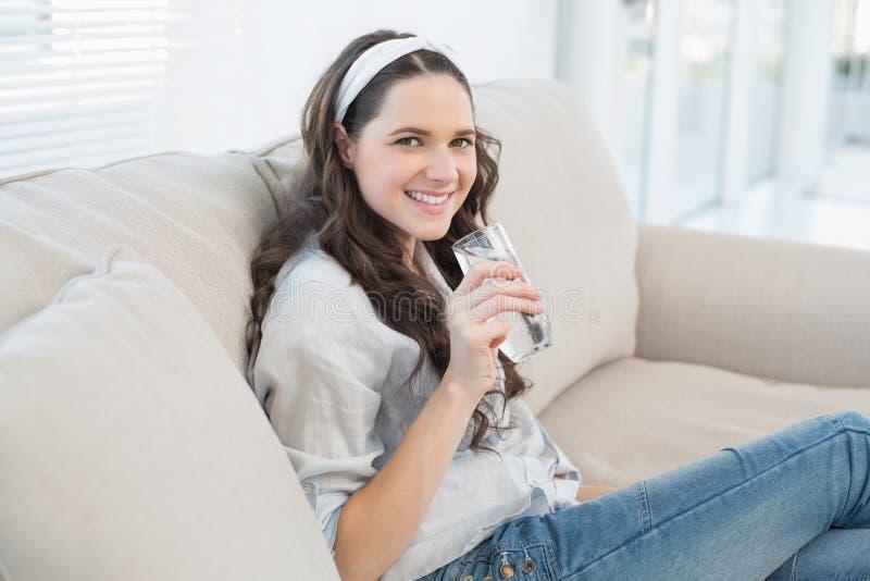 Шикарная вскользь женщина на cosy кресле держа стекло воды стоковые изображения