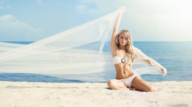 Шикарная, горячая девушка в белом бикини представляя на пляже с дуновением стоковая фотография rf