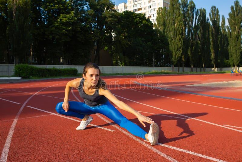 Шикарная девушка пригонки протягивая перед гонкой на стадионе, пустым s стоковая фотография