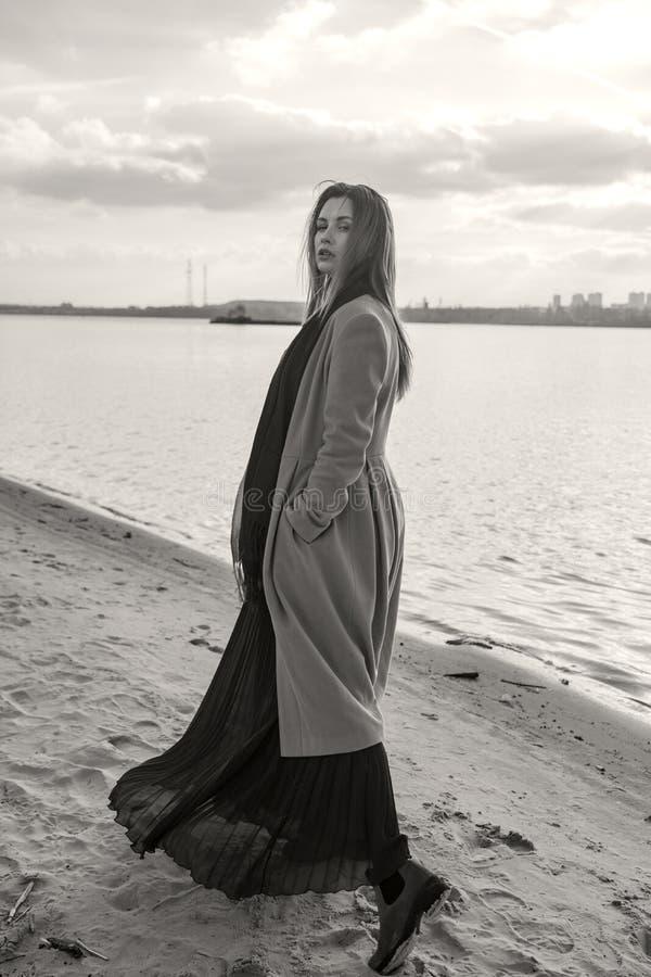 Шикарная европейская женщина в теплых пальто и платье на прогулке в парке около реки Ветреная погода Ее одежды летают в ветер Гру стоковое изображение