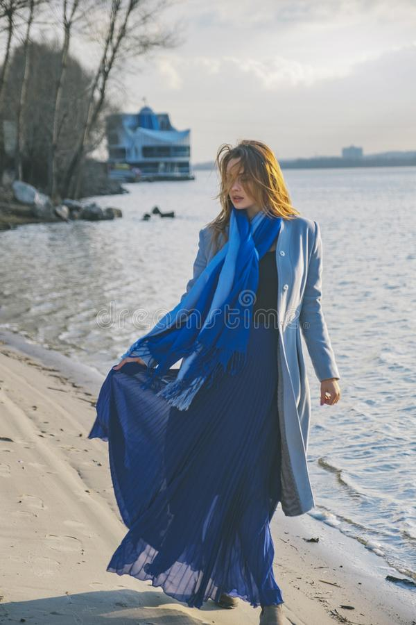 Шикарная европейская женщина в теплых пальто и платье на прогулке в парке около реки Ветреная погода Ее одежды летают в ветер Гру стоковая фотография rf