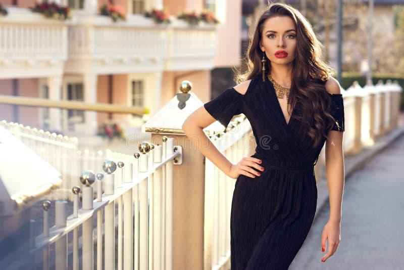 Шикарная женская модель в черном платье с вырезом взваливает на плечи стоковое изображение