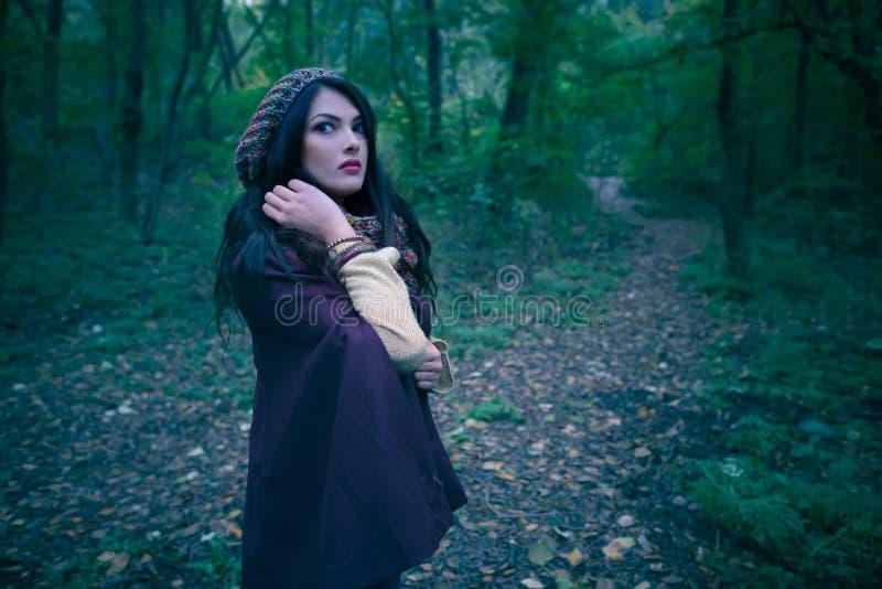 Шикарная женщина вспугнутая в лесе осени в вечере Сиротливая женщина в древесинах Девушка бежать далеко от опасности глубоко внут стоковое изображение rf