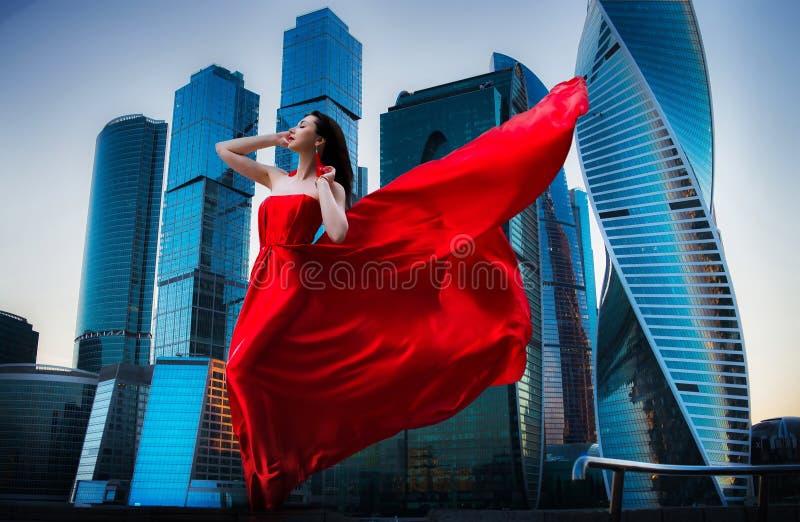 Шикарная женщина в красном выпорхнутом платье : m стоковое фото rf