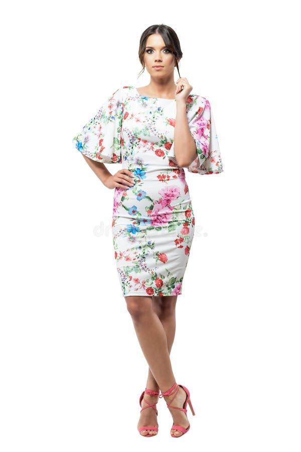 Шикарная женщина в платье вечера при цветочный узор стоя с пересеченными ногами стоковая фотография rf