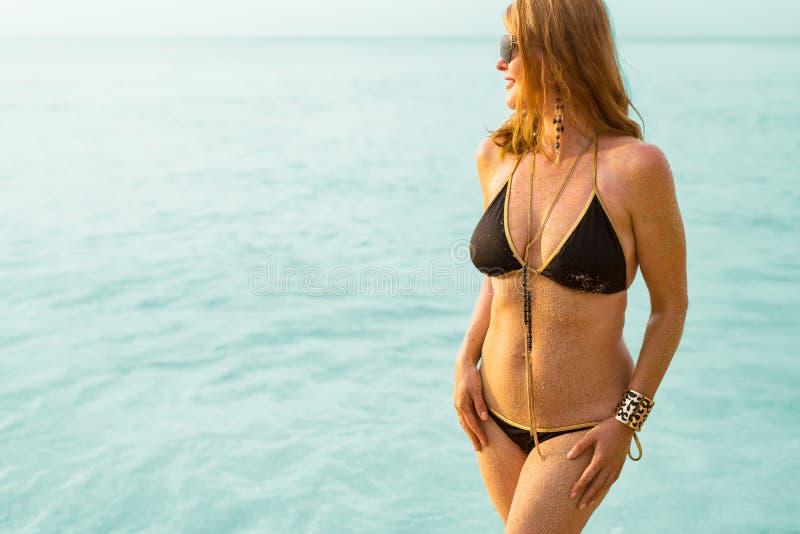 Шикарная женщина в черных бикини и украшениях морем стоковое изображение rf