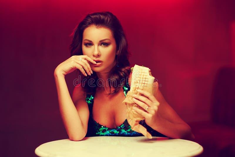 Шикарная женщина есть kebab в ночном клубе стоковая фотография