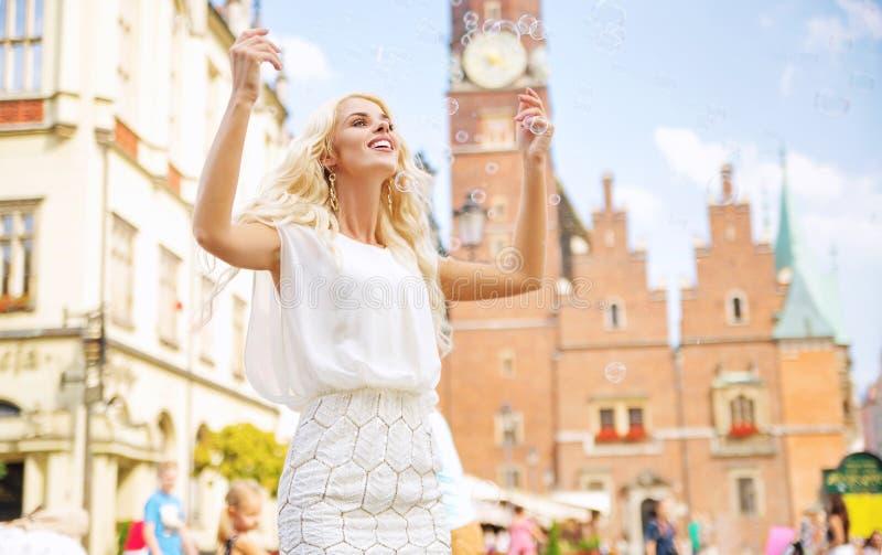 Шикарная женщина делая пузыри мыла стоковое фото rf