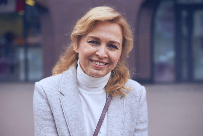Шикарная зрелая женщина усмехаясь на камере стоковое фото