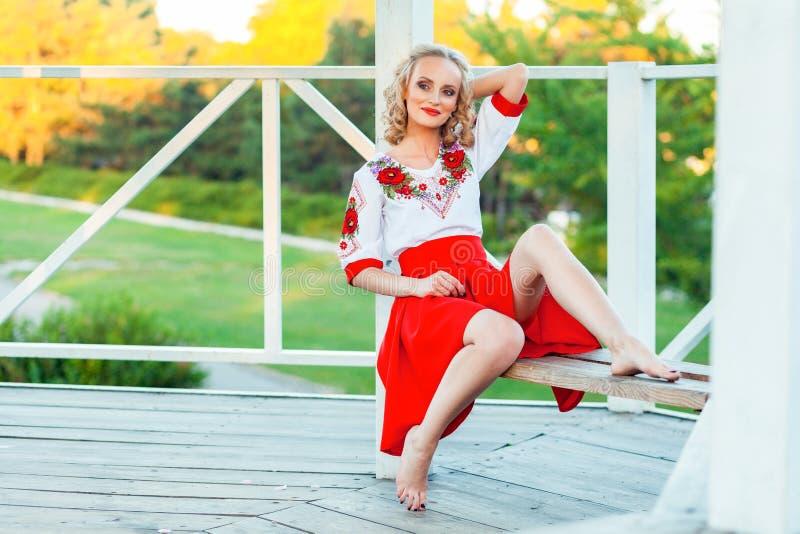 Шикарная молодая белокурая женщина с макияжем, курчавым стилем причесок в стильном красном белом платье представляя на стенде в б стоковые фото