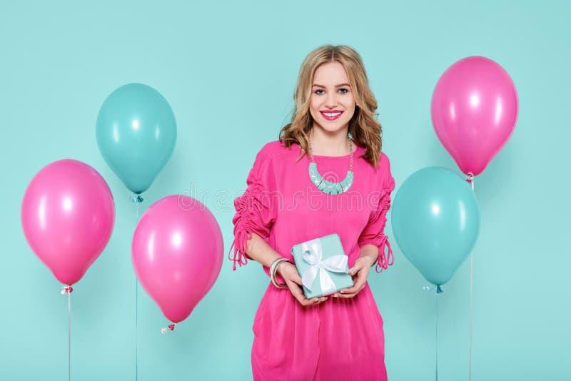 Шикарная молодая женщина в обмундировании партии держа настоящий момент изолированный над пастельной синью покрасила предпосылку  стоковые фотографии rf