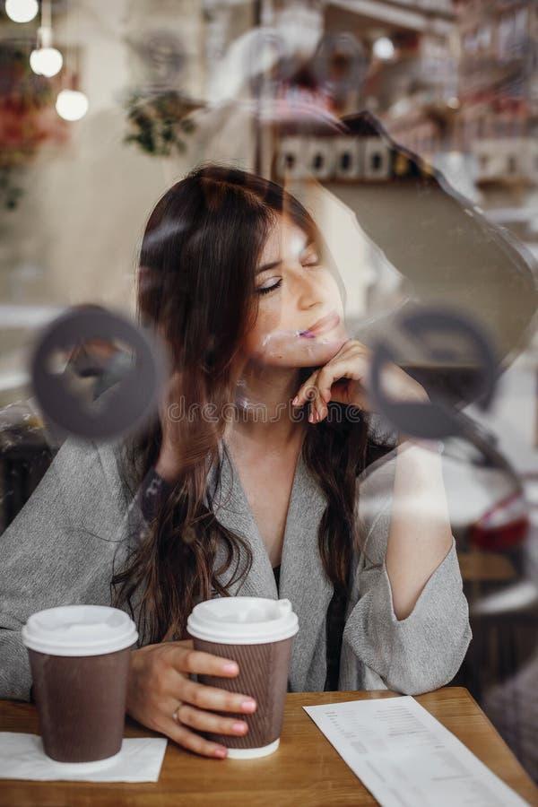 Шикарная молодая женщина с чашкой кофе сидя в кафе и реальной стоковые фото