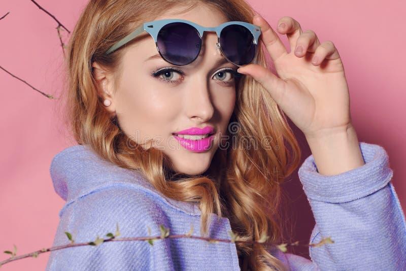 Шикарная молодая женщина с белокурым вьющиеся волосы и нежным составом, в элегантных одеждах с аксессуарами стоковое фото rf