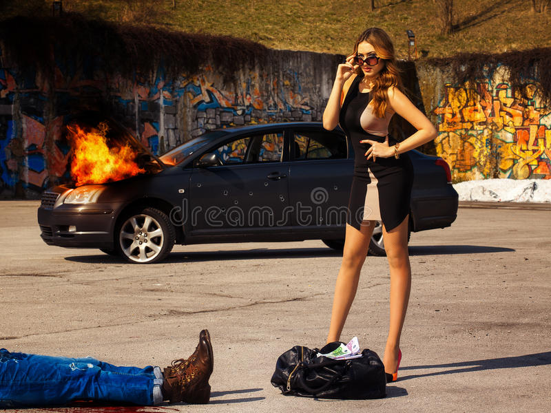 Шикарная молодая стойка взрослой женщины около сумки вполне денег позади стоковая фотография