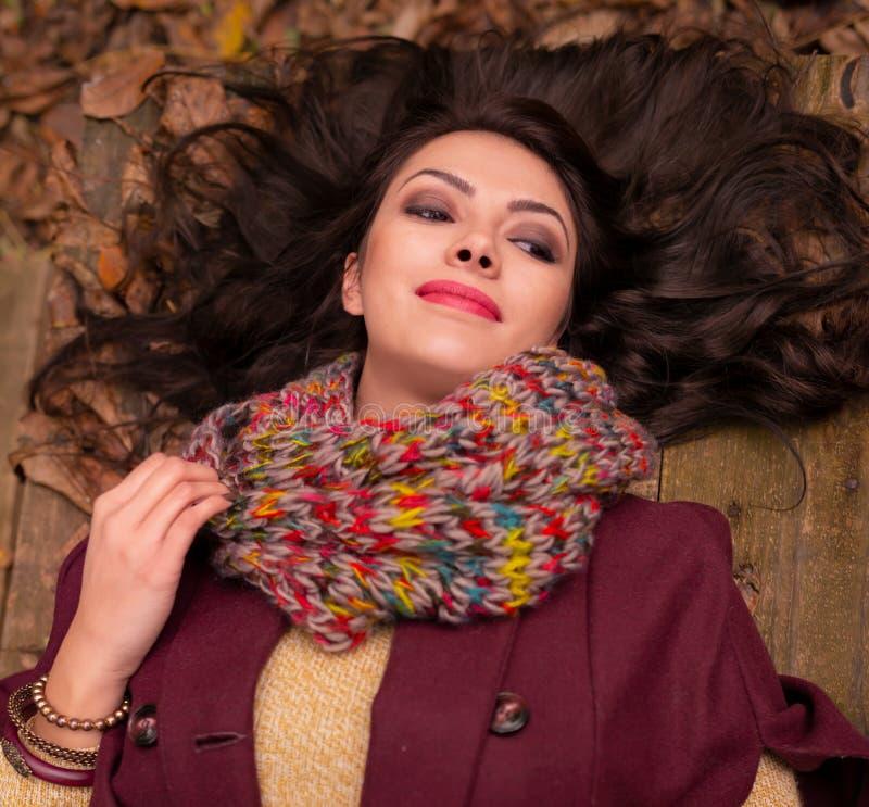 Шикарная романтичная молодая женщина с красивыми длинными каштановыми волосами, лежа вниз на деревянном столе в лесе осени стоковая фотография rf