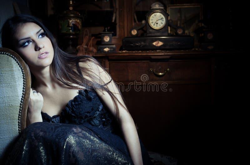 Шикарная сексуальная женщина брюнет в винтажном интерьере с винтажным шкафом и старыми часами в предпосылке и составе сидя в стул стоковое фото