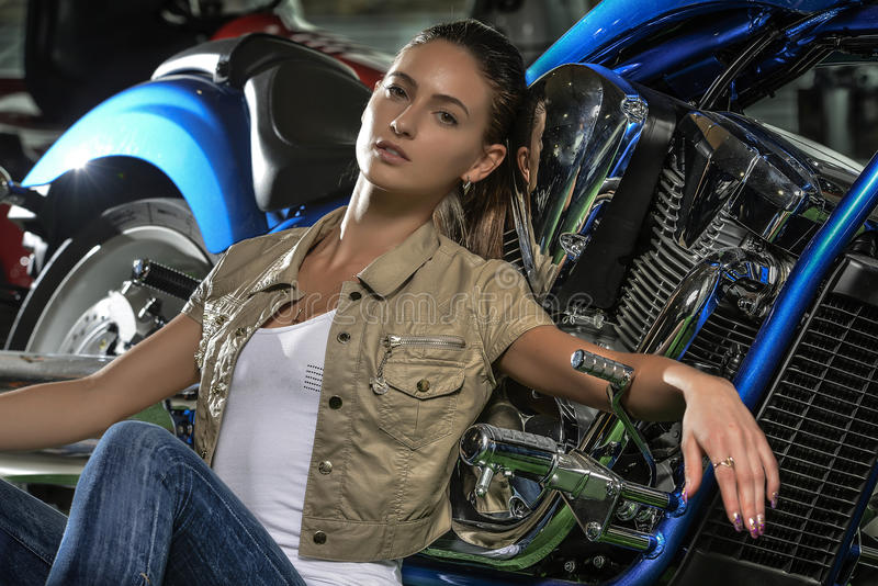 Шикарная склонность женщины против ее голубого мотоцикла стоковое изображение