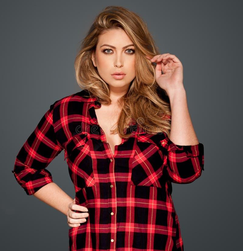 Шикарное белокурое в рубашке проверенной красным цветом стоковая фотография