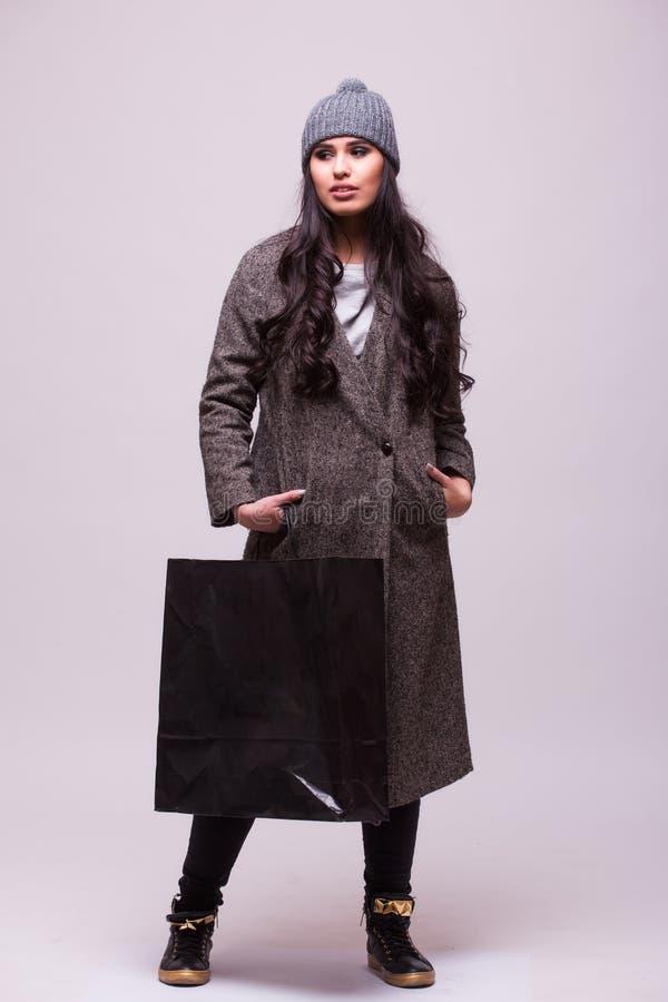 Шикарное молодое брюнет держа хозяйственную сумку стоковые фотографии rf