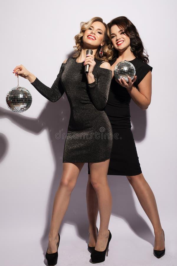 Шикарные молодые женщины в праздничных платьях поя караоке стоковые изображения rf