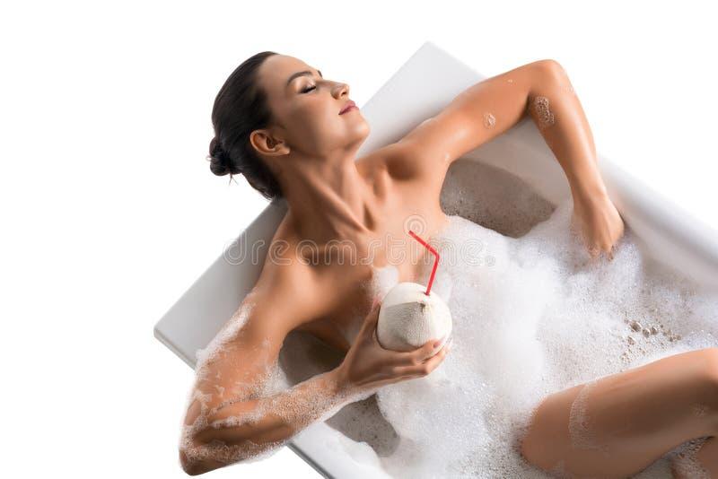Шикарный брюнет в ванне и коктейле пены стоковые фотографии rf
