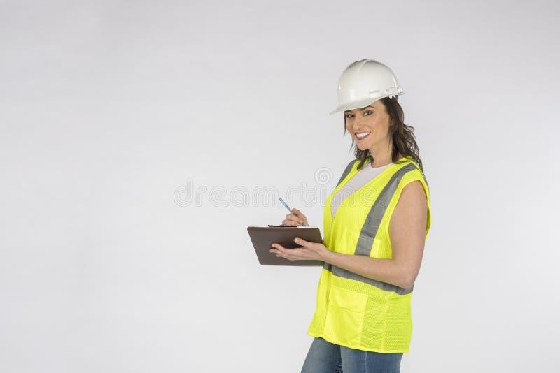 Шикарный рабочий-строитель брюнета представляя против белой предпосылки стоковые изображения