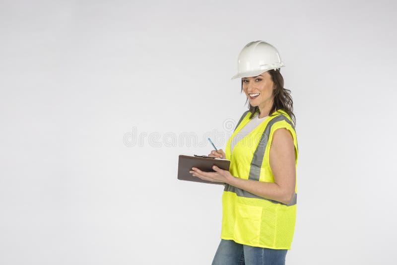 Шикарный рабочий-строитель брюнета представляя против белой предпосылки стоковая фотография rf