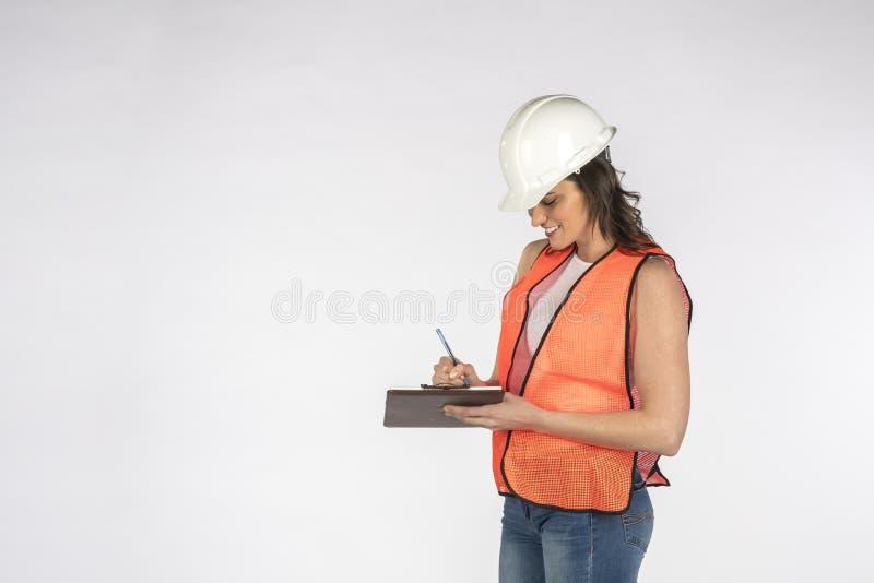 Шикарный рабочий-строитель брюнета представляя против белой предпосылки стоковое фото rf