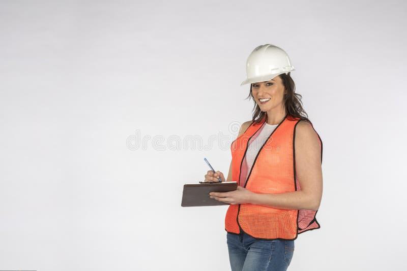 Шикарный рабочий-строитель брюнета представляя против белой предпосылки стоковая фотография