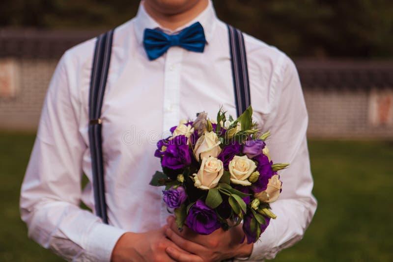 Шикарный усмехаясь groom andsome groom на невесте смокинга свадьбы ждать Элегантный человек в белых рубашке и бабочке стоковые фотографии rf