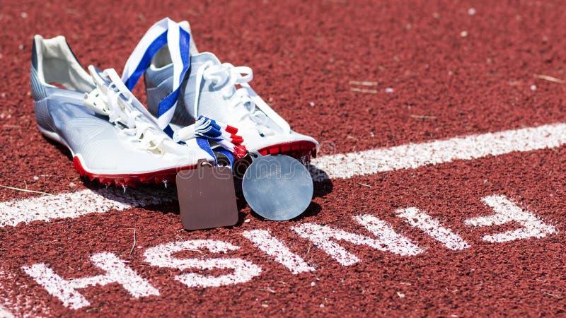 Шипы следа с медалями на финишной черте стоковые фотографии rf