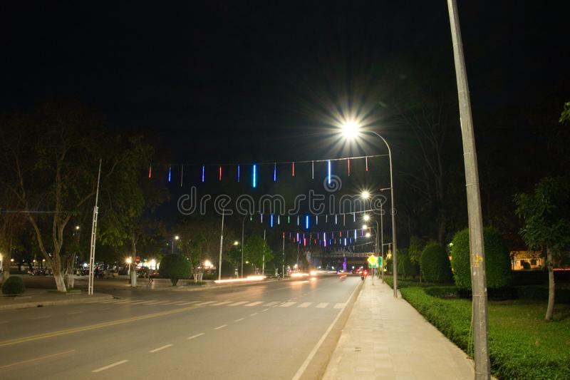 Широкая и прямая улица города вечером освещенного фонариками Дорожная разметка Декоративные света над дорогой стоковые изображения