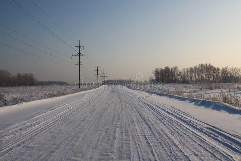 Широкая освобоженная дорога зимы пустыни между деревнями среди полей покрытых со снегом с высоковольтными башнями на обочине стоковое изображение