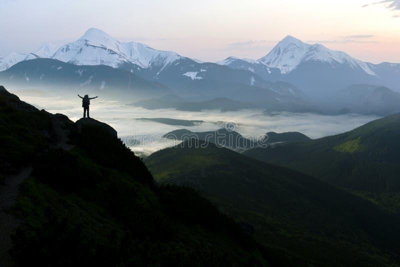 Широкая панорама горы Небольшой силуэт туриста с рюкзаком на наклоне скалистой горы с поднятыми руками над покрытой долиной стоковые изображения rf