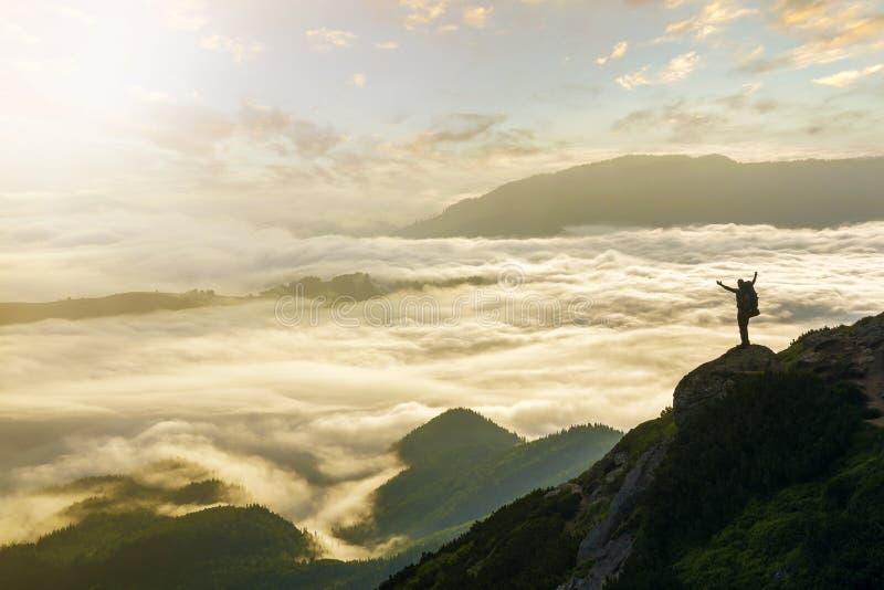 Широкая панорама горы Небольшой силуэт туриста с рюкзаком на наклоне скалистой горы с поднятыми руками над покрытой долиной стоковое изображение rf