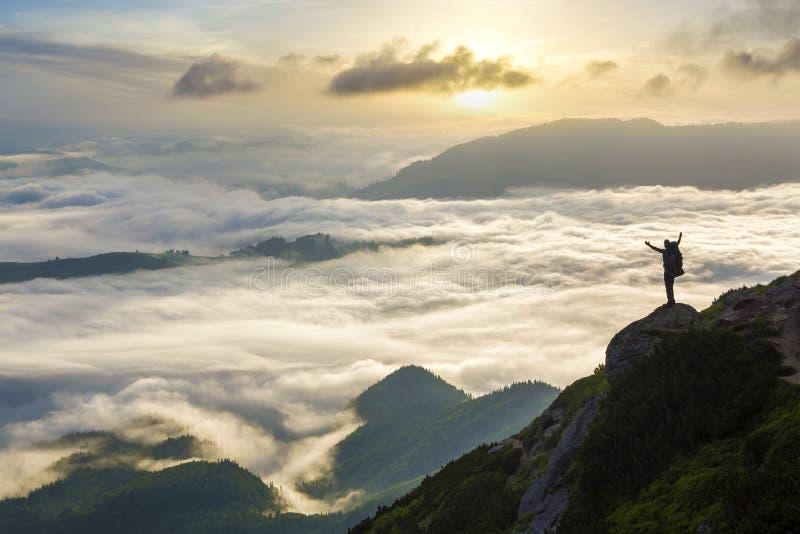 Широкая панорама горы Небольшой силуэт туриста с рюкзаком на наклоне скалистой горы с поднятыми руками над покрытой долиной стоковое фото rf