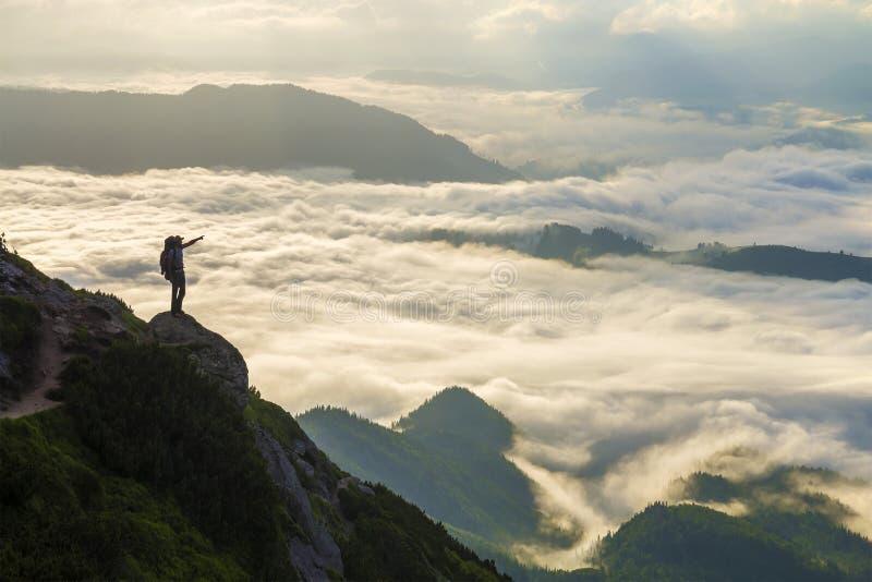 Широкая панорама горы Небольшой силуэт туриста с рюкзаком на наклоне скалистой горы с поднятыми руками над покрытой долиной стоковые изображения