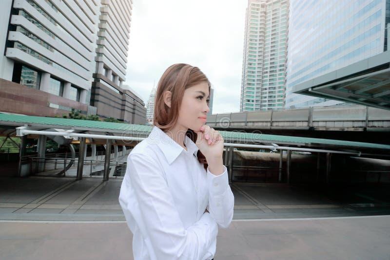 Широкий ангел снял уверенно молодой азиатский представлять женщины стоя и думая на городской предпосылке публики здания стоковые фото