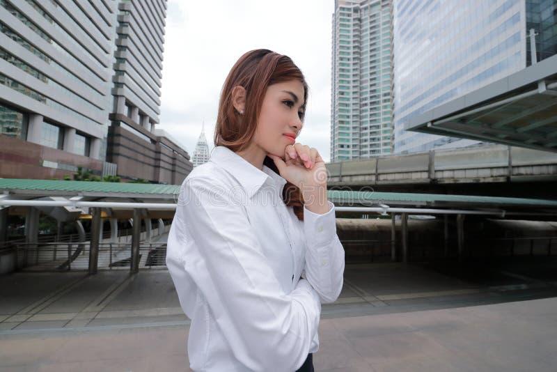 Широкий ангел снял уверенно молодой азиатской женщины с белой рубашкой на городской предпосылке публики здания стоковое изображение