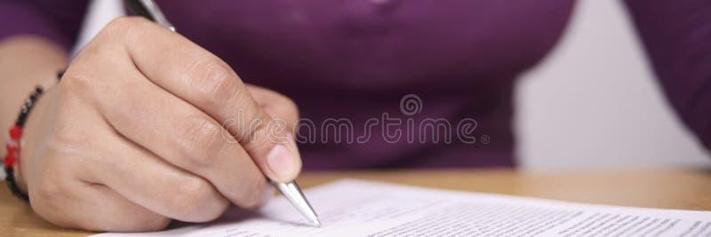 Широкий взгляд контракта подписания коммерсантки стоковое изображение rf