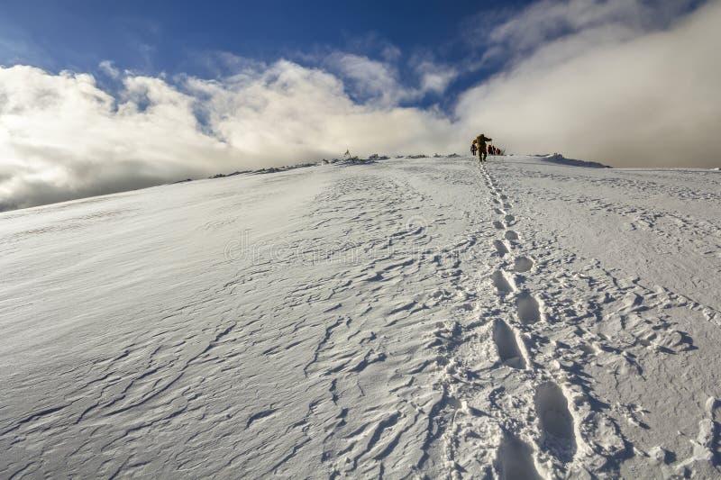 Широкий взгляд на снежном холме при следы ноги и далекий hiker идя вверх с рюкзаком в горах стоковые фото