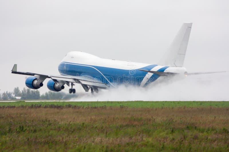 Широкий самолет груза тела принимает в проливной дождь выходя за облаком splatter стоковая фотография rf