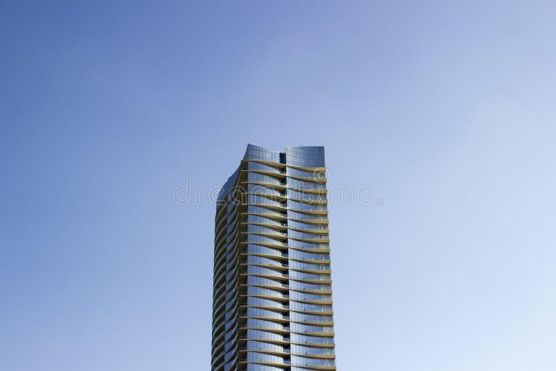 Широкое вид спереди современного корпоративного офисного здания высотного здания с желтоватыми свисаниями в каждом поле стоковое фото rf