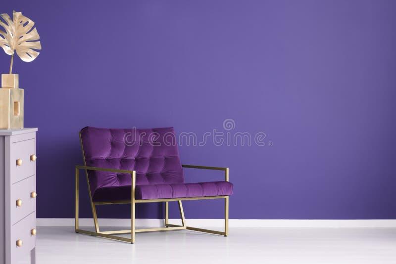 Широкое кресло, комод ящиков и золотые украшения установили на a стоковая фотография
